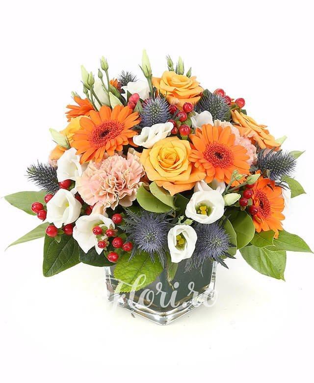 5 trandafiri portocalii, 4 gerbera portocalie, 3 lisianthus alb, 5 garoafe portocalii, 5 hypericum roșu, eryngium, verdeață